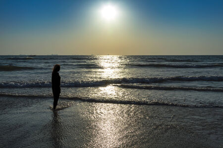 dawning: Scenic view from beach in Goa to beautiful sunrise above the Arabian sea. Silhouette of woman or girl looks at sea