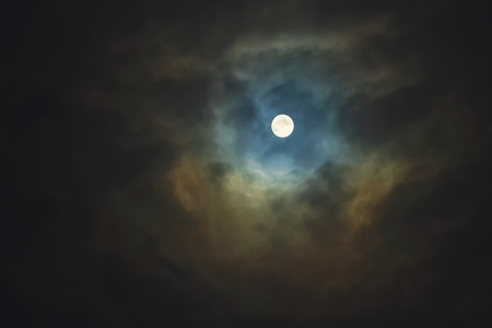 Full moon shines through dramatic sky surrounded clouds photo