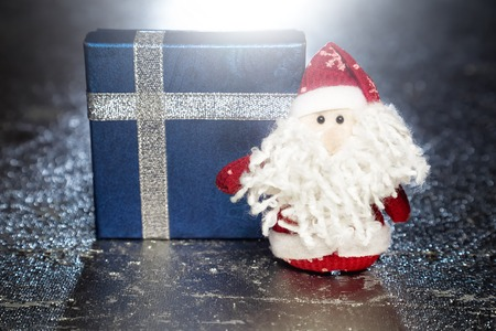 Christmas Santa Claus or Father Frost and blue gift box or present on silver or metal grunge surface with backlight from behind photo