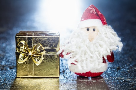 Christmas Santa Claus or Father Frost and gold gift box or present on silver or metal grunge surface with backlight from behind photo