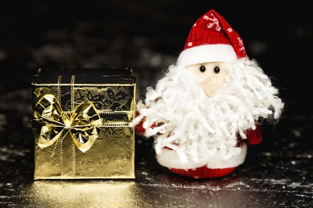 Christmas Santa Claus or Father Frost and gold gift box or present on silver or metal grunge surface photo