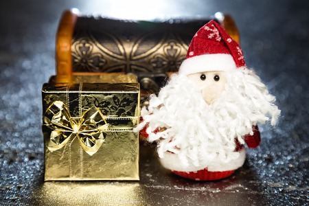 Christmas Santa Claus or Father Frost with gold gift box or present and chest on silver or metal grunge surface with backlight from behind photo