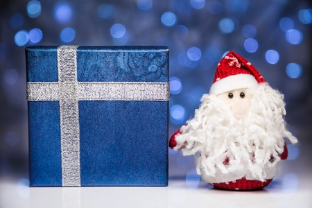 Santa Claus or Father Frost and blue gift box or present on christmas lights background photo