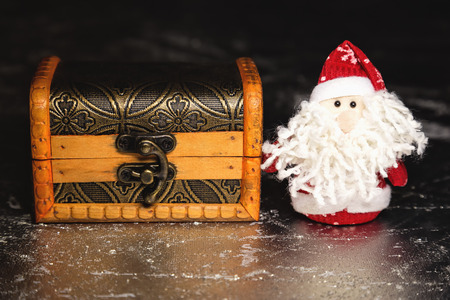 Christmas Santa Claus or Father Frost and wooden chest on silver or metal grunge surface photo