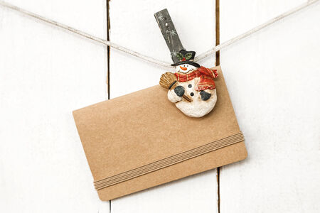 Christmas snowman clothespins hanging on clothesline or rope and holding greeting brown craft paper card on wooden background photo