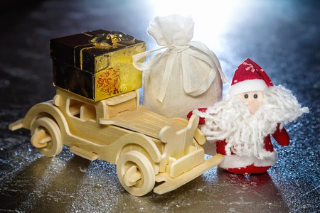 Santa Claus with old vintage wooden automobile, gift box and sack on silver or metal grunge surface with backlight from behind. Main focus of image on Santa Claus photo