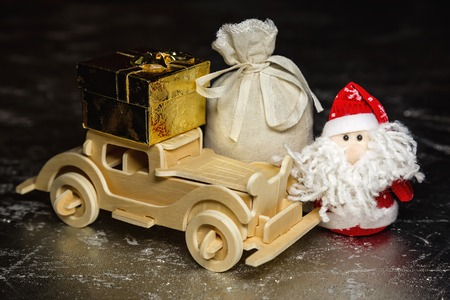 Santa Claus with old vintage wooden automobile, gift box and sack on silver or metal grunge surface. Main focus of image on Santa Claus photo