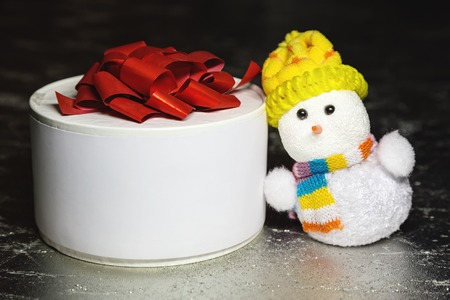 Christmas snowman toy and white gift box or present on silver or metal grunge surface photo