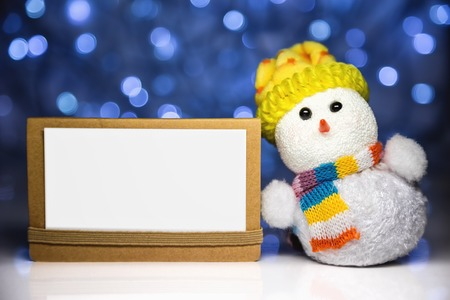 Christmas snowman toy and greeting white blank card on craft paper with blurred Christmas lights on background photo