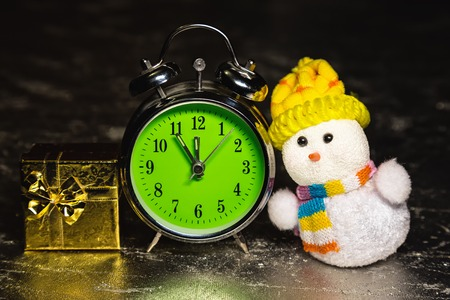 Christmas snowman toy with gold gift box or present and old vintage alarm clock on silver or metal grunge surface. Showing time five minutes before twelve midnight photo