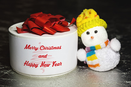 Christmas greeting card with snowman toy and white gift box or present on silver or metal grunge surface photo