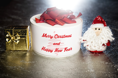 Christmas greeting card with Santa Claus or Father Frost with gold and white gift boxes or presents on silver or metal grunge surface with backlight from behind photo