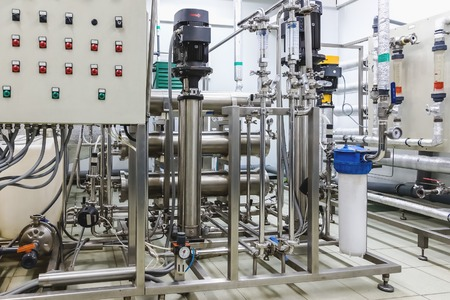 distillation: Pipes, pump and control panel in conditioning or distillation room on pharmaceutical industry or chemical plant Stock Photo