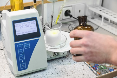 Laborant makes test in research laboratory with electronic measuring equipment on pharmaceutical industry manufacture or chemical plant