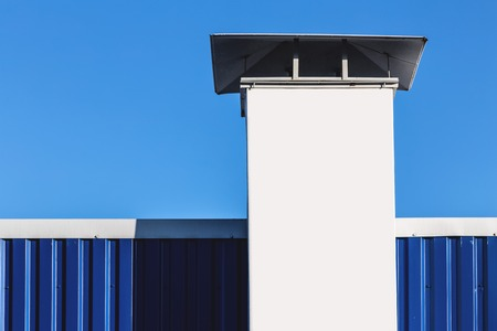 White chimney on building rooftop on blue sky background photo
