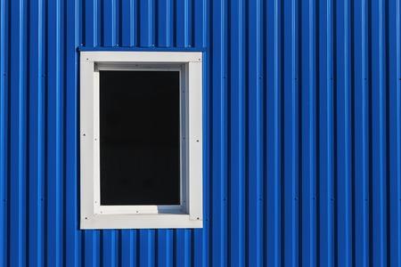 White window in blue color metal siding wall Archivio Fotografico