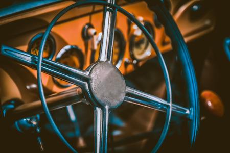 Steering wheel in interior of retro or old automobile. Processed by vintage or retro effect filter Archivio Fotografico