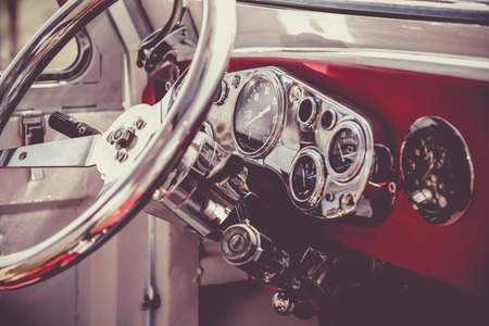 Interior of old retro vintage automobile or car with steering wheel and dashboard. Processed by vintage or retro effect filter