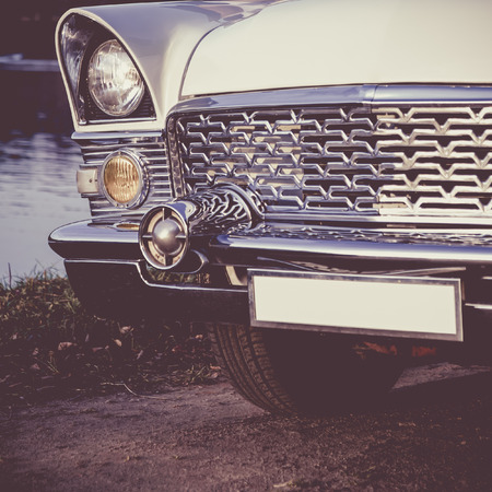 car grill: Old retro or vintage car or automobile front side with front lights or headlights and radiator grill. Processed by vintage or retro effect filter