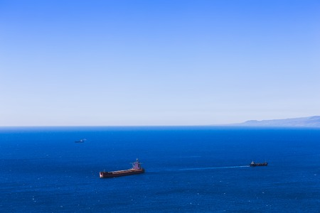 Empty container cargo ship vessels and in the open Atlantic ocean. Coast or shore of island at background Archivio Fotografico