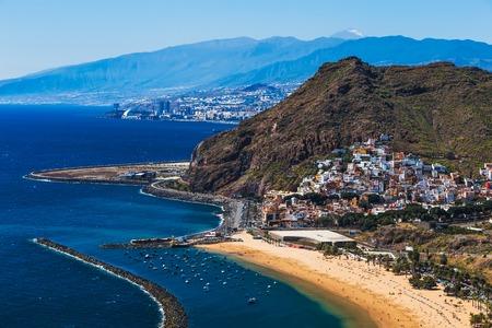 Coast or shore of Atlantic ocean and beach Las Teresitas in Santa Cruz city on Tenerife Canary island, Spain at spring or summer. Teide volcano at background