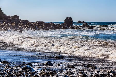 wild canary: Waves and foam on wild stone beach on coast or shore of the Atlantic ocean with sky and rock on skyline or horizon in Tenerife Canary island, Spain Stock Photo