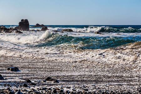 wild canary: Waves and foam on wild stone beach on coast of the Atlantic ocean with sky and rock on skyline or horizon in Tenerife Canary island, Spain at spring or summer