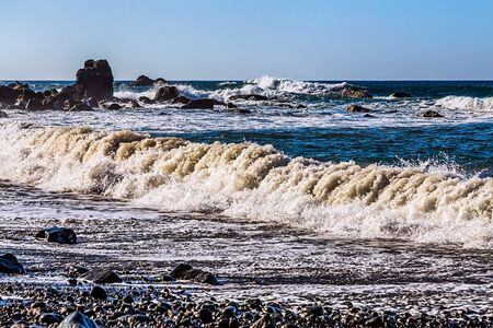 wild canary: Waves and foam on wild stone beach on coast or shore of the Atlantic ocean with sky and rock on skyline or horizon in Tenerife Canary island, Spain at spring or summer