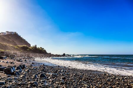 wild canary: Wild stone beach on coast or shore of the Atlantic ocean with waves and blue sky and skyline or horizon in Tenerife Canary island, Spain Stock Photo