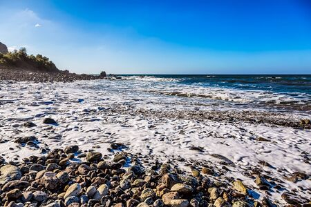 wild canary: Wild stone beach on coast or shore of the Atlantic ocean with waves and foam and blue sky and  horizon in Tenerife Canary island, Spain at spring or summer Stock Photo