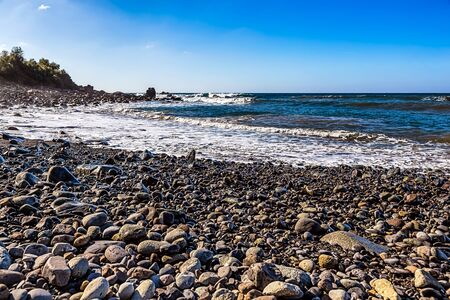 wild canary: Wild stone beach on shore of the Atlantic ocean with waves and sky with clouds and skyline or horizon in Tenerife Canary island, Spain at spring or summer