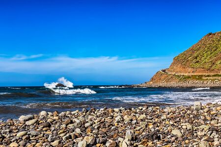 wild canary: Wild stone beach and mountain on coast or shore of the Atlantic ocean with waves and sky with clouds and skyline or horizon in Tenerife Canary island, Spain at spring or summer