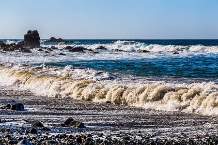 wild canary: Waves and foam on wild stone beach on shore of the Atlantic ocean with sky and rock on skyline or horizon in Tenerife Canary island, Spain at spring or summer