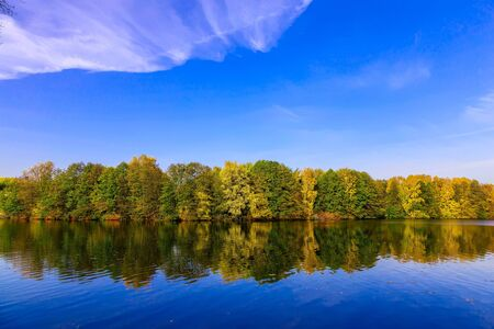 bushy: Autumn Scenery with Bushy Colourful Trees and Cloudy Blue Sky Reflected in Lake at Sunny Day Stock Photo
