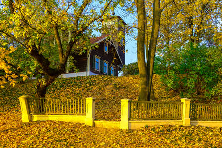 Country Home with Fence on Knoll in Fallen Leaves In Autumn
