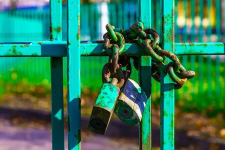padlocked: Main Focus of Image on Metal Fence with Rusty Lock and Chain on Blurred Background Stock Photo