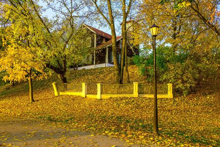 knoll: Country Home with Fence on Hillock with Fallen Leaves In Autumn