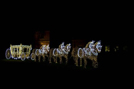 illuminated: Illuminated Sculptures of Horses with Carriage in Street Stock Photo