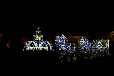 sculptures: Illuminated Sculptures of Horses with Carriage and Fountain in Street