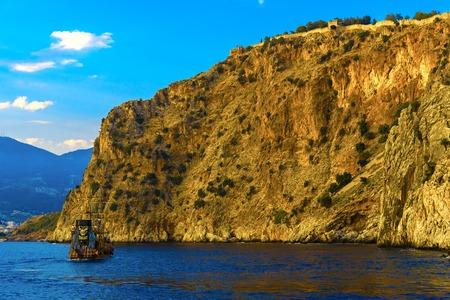 Sailing ship decorated as a pirate on background of rock at sundown in Alanya, Turkey Stock Photo