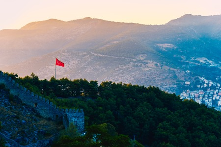 View of Turkish flag on castle of Alanya on top of mountains at sunny day, Turkey Archivio Fotografico