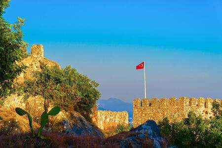 Turkish flag on castle of Alanya on top of mountains on background of blue sky, Turkey Archivio Fotografico