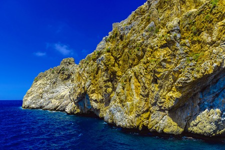 View of cliffs on background of blue sky from sea at sunny day in Alanya, Turkey