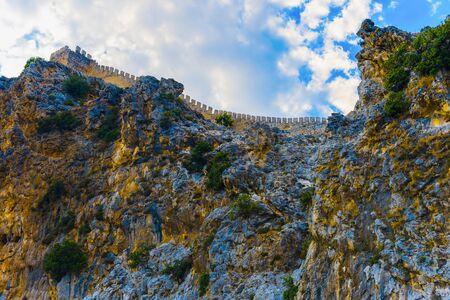 Part of fortress on rocky coast of Alanya on background of sky, Turkey