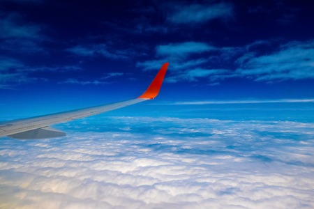 Aircraft or Plane Wing on Cloudscape View above the Clouds background Stock Photo