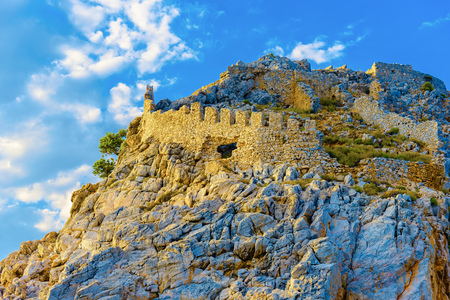 Ruins of castle at top of rock on background of sky at sunset in Alanya, Turkey