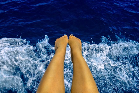 Woman holding her feet above sea during boat trip in Alanya, Turkey
