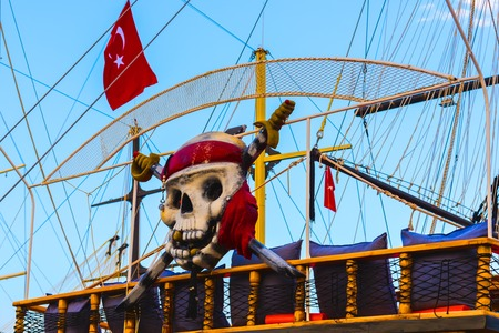 Tourist ship with Turkish flag and decorated as pirate skull and crossbones in Alanya, Turkey Archivio Fotografico