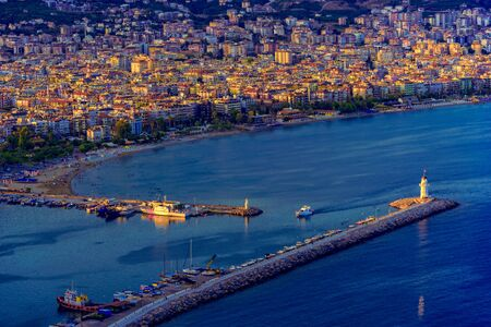 View of Alanya coastline and port  with lighthouse at sunset, Turkey Stock Photo