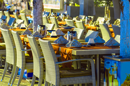 Restaurant tables and chairs on street in Alanya at sunny day, Turkey Archivio Fotografico
